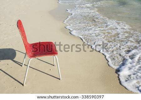 An Empty Single Red Chair at Tropical Coastline Beside Ocean Soapy White Waves - stock photo