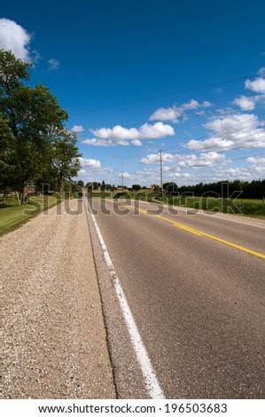 An empty stretch of road which disappears down a hill in the distance. - stock photo