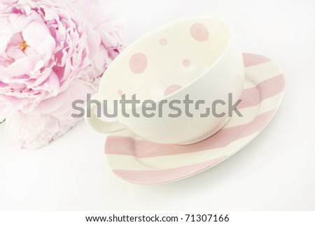 An empty tea cup with a pink Peony in the  background with shallow depth of field, copy space - stock photo