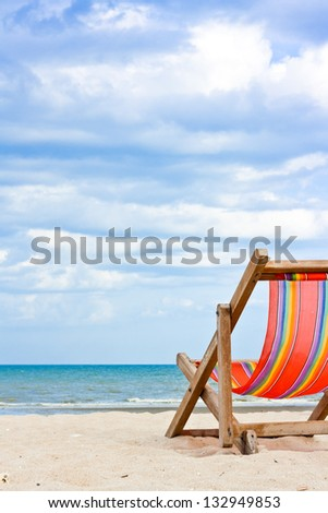 An empty wooden beach chair at the beach - stock photo