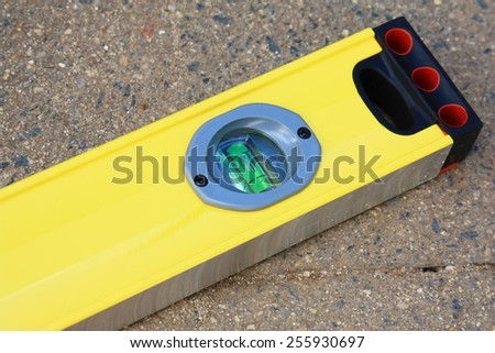 an end view of yellow spirit level on the bricks - stock photo