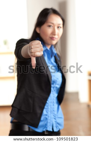 An energetic cute young Asian woman with enthusiastic expression wearing a black suit and blue shirt. - stock photo