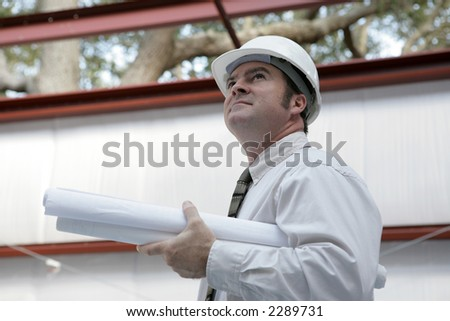 An engineer or architect holding blueprints surveying his project.  Building is steel frame construction. - stock photo