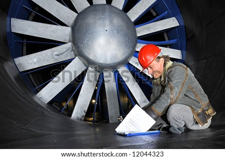 An engineer, wearing a hardtop, going through his notes in front of a huge industrial wind tunnel rotor - stock photo