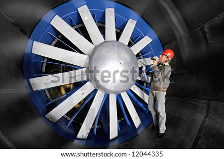An engineer, wearing a red hardtop, inspecting a wind tunnel from up close - stock photo