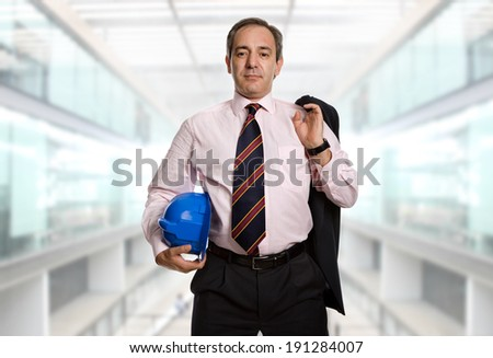 An engineer with blue hardhat at the office - stock photo
