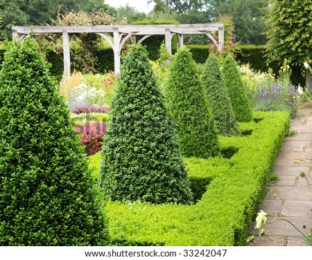 An English Landscape garden in Summer with Box Hedging and Topiary - stock photo