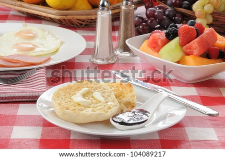 An English muffin with fruit salad and a Canadian bacon and egg breakfast - stock photo