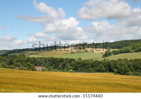 An English Rural Landscape with ripening Corn in the fields and a farm in the distance - stock photo
