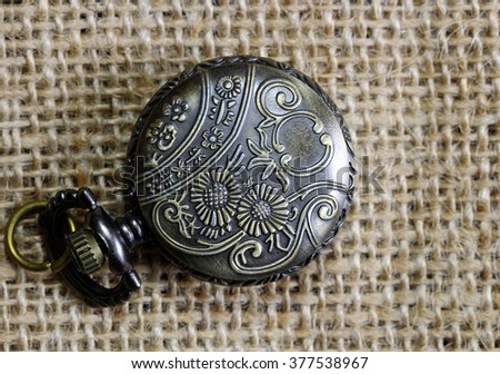 An engraved pocket watch on a burlap cloth. - stock photo
