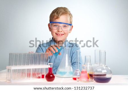 An enthusiastic boy looking at camera during experiment - stock photo