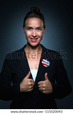 An enthusiastic woman in a suit charcterizing someone who just voted - stock photo