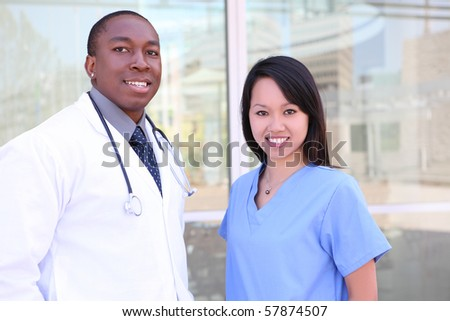 An ethnic happy medical man and woman team outside hospital - stock photo