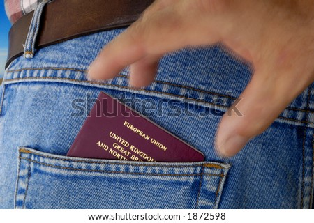 An EU passport pokes out of the rear pocket of a traveller's jeans. Motion blur on a pickpocket's hand, about to take it. - stock photo