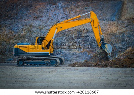 An excavator working removing earth on a construction site. - stock photo