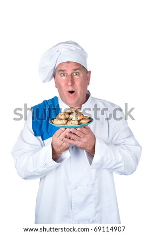 An excited chef with plate of cookies isolated on white. - stock photo