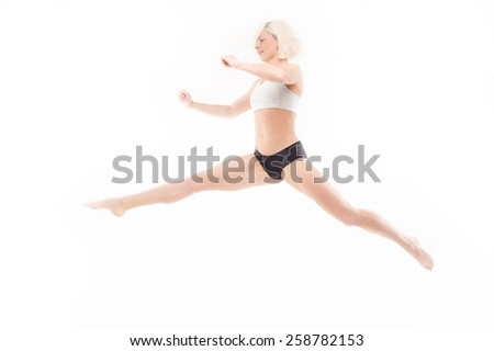 An excited young sportswoman leaping for joy while isolated on a white background - stock photo