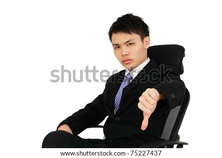 An executive showing thumbs down while sitting on a chair - stock photo