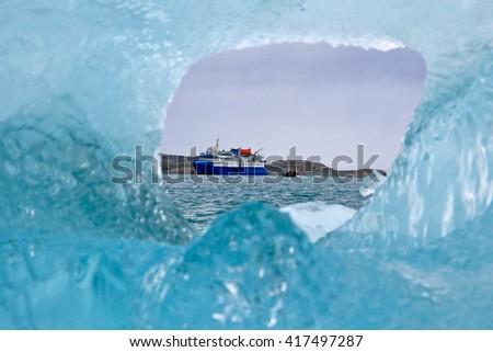 An expedition ship seen through a hole in an iceberg    - stock photo