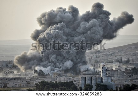 An explosion after an apparent US-led coalition airstrike on Kobane, Syria, as seen from the Turkish side of the border, near Suruc district, 13 October 2014, Turkey , Syria. - stock photo