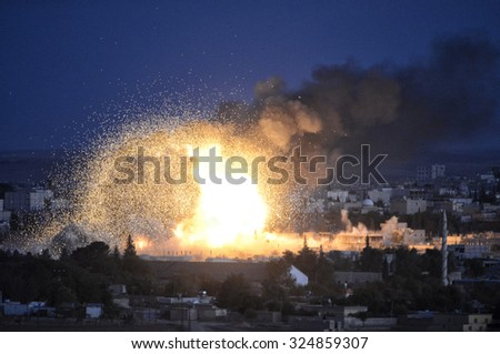 An explosion after an apparent US-led coalition airstrike on Kobane, Syria, as seen from the Turkish side of the border, near Suruc district, 20 October 2014, Turkey , Syria. - stock photo