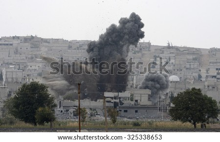 An explosion after an apparent US-led coalition airstrike on Kobane, Syria, as seen from the Turkish side of the border, near Suruc district, 21 October 2014, Sanliurfa, Turkey  - stock photo