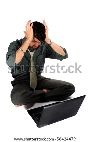 An expression of an Indian business executive after making a mistake on his laptop computer. Also metaphorical as expression after seeing business loss, on white studio background. - stock photo