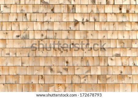 An exterior wall of newer wood cedar shingles. - stock photo