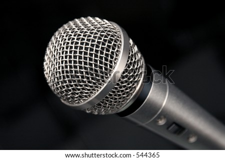 an extreme closeup view of a microphone on a black background - stock photo