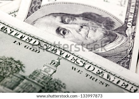 """An extreme macro shot of 100 US$ money notes, depicting the writing """"Untied States of America"""" and the portrait of Benjamin Franklin defocused in the background. Shallow depth of field. - stock photo"""
