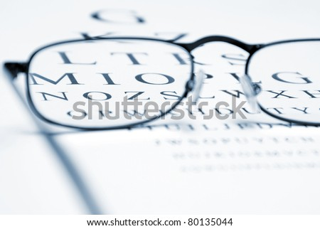 An eye chart with a pair of glasses and selective focus within the frames to emphasize vision correction. - stock photo