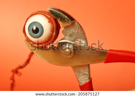 An eyeball feels the squeeze of a pair of pliers. - stock photo