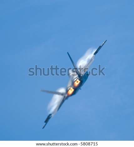An F-22 Raptor fighter with vapor trail, seen through the wavy heat of the plane's exhaust - stock photo