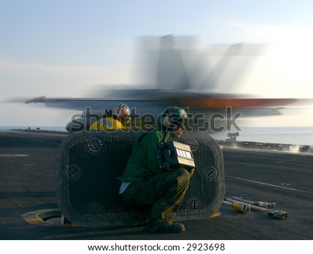 An F-18 Super Hornet rockets down the catapult track of a nuclear powered aircraft carrier - stock photo