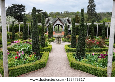 An Formal Landscape garden with Box Hedging and colorful flowerbeds and Topiary - stock photo