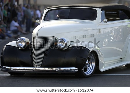 An fully restored classic Chevy cruises the main drag in a car show. - stock photo