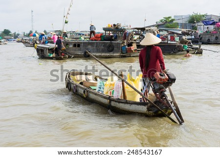 An Giang, Vietnam - Nov 30, 2014: Local people sell fruit and daily essential item on rowing or motorboat at floating market on river in Mekong delta, southern Vietnam - stock photo