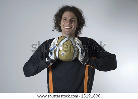 An goalie holding a soccer ball between gloved hands.  He is smiling and looking directly at the camera. Horizontally framed shot. - stock photo