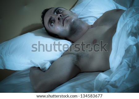 an handsome and muscular man sleeping peacefully in a bed - stock photo