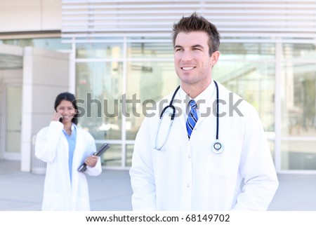 An handsome doctor with woman coworker nurse in background - stock photo