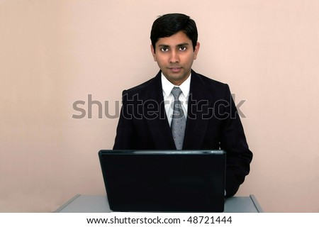 An handsome Indian businessman working on a laptop - stock photo