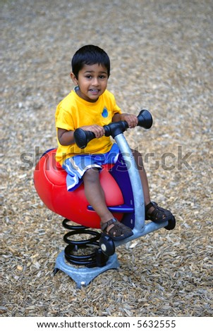 an handsome Indian child happy playing in the play area - stock photo