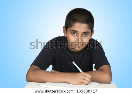 An handsome Indian kid doing his homework diligently - stock photo