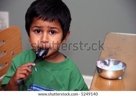 An handsome indian kid enjoying his yoghurt - stock photo