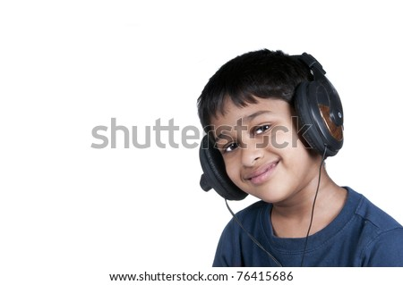 An handsome Indian kid enjoying music  - concept of education, audio aid, learning, music etc. - stock photo