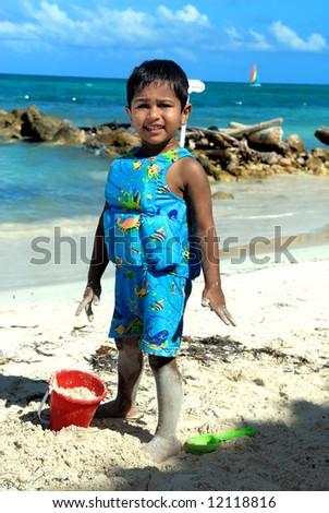 An handsome Indian kid having fun at a tropical beach - stock photo