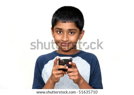 An handsome Indian kid playing games with teh cell phone - stock photo