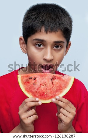 an handsome indian kid savoring a watermelon, a healthy diet - stock photo