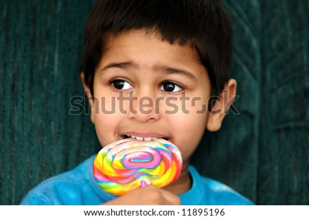An handsome Indian kid savoring his colorful candy - stock photo