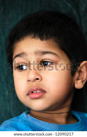An handsome Indian kid sitting very moody - stock photo